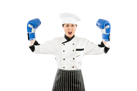 strong aggressive cooking chef woman concept. chef cook wearing boxing gloves showing flexing muscles wearing clothing. asian female model isolated on white background with copyspace.