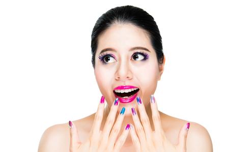 興奮している女性モデルは表示 copyspace と白い背景の上の口と目の焦点を開く明るい赤い唇の近く彼女のグラデーションの色の爪です。 写真素材