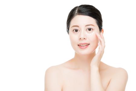 De jonge Aziatische Chinese oogcrème van het damegebruik handhaaft jonge leeftijd en houdt de huid beter helder geïsoleerd op witte achtergrond. mode schoonheid en gezondheid concept. Stockfoto