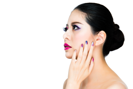 brunette hair rainbow eyeshadow asian lady showing beauty nails and focused on copyspace on white background. concept advertising about make-up.