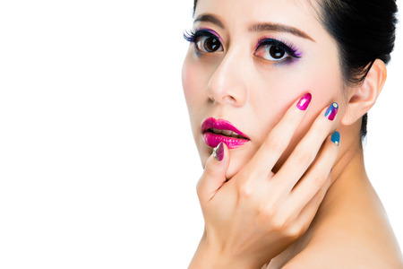 asia beautiful woman with multicolored fingernails and putting on stylish face make-up eyeshadow and pink lipstick. isolated on white background.