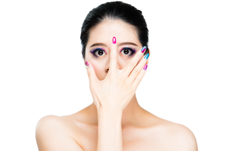 beautiful asian lady showing colorful fingernail and covered face display rainbow eyeshadow standing copyspace on white wall. Stock Photo - 78290818