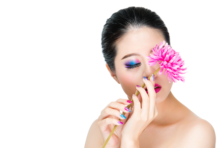 stylish holding fresh flower with beautiful nails and closed eyes display presenting gradient color eye makeup isolated on white background. Stock Photo