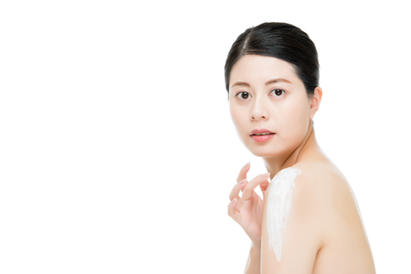 beauty fashion asian chinese woman applying moisturizing body lotion for soften skin isolated on white background. fashion beauty and health concept. Stock Photo