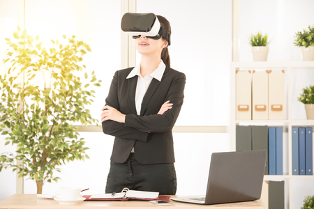 asian office lady standing on the office experience virtual reality device by VR headset glasses smiling watching 3D video on screen with bright background. Stock Photo
