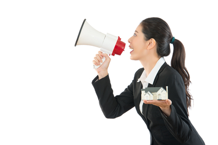 peddle: house company agent holding big megaphone talking latest information about estate on the blank wall copyspace and showing 3d model of building isolated on the white background.