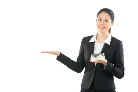 enthusiastic young girl holding house model and showing new estate news on white background. friendly agent help someone searching apartment.