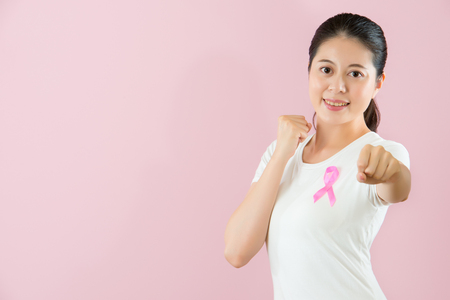 Cheerful and open minded Chinese Asian young girl make a fist elongation of her arms showing the positive faith and fighting for cancer isolated on pink background. medical and health concept.