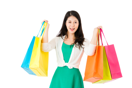 smiling lady showing many shopping paperbags after leaving mall center auctions feeling satisfied on the white wall with copyspace background. Stock Photo