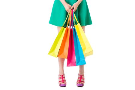 ショッピング女性空 copyspace 区域の多くのカラフルなバッグ スタンドを保持している白い背景に分離されました。ショッピング フェスティバルの広