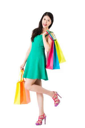 若い女性キャリー ショッピング バッグの肩と手は愉快白い壁の空の領域の上に立つし、芸術的なハイヒールで足を上昇します。