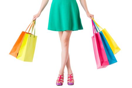 両手の買い物袋の多くを示す緑のドレス女性のセクション低クロス脚の空の領域での copyspace と白い背景で隔離。