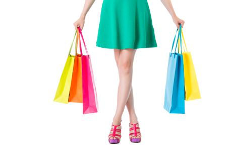 美容女性で足 shopbags 半分の体に白い背景の上の緑のドレス女の子持株提示は、空の領域で撮影。 写真素材