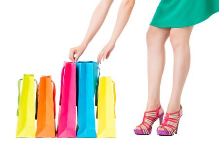 両手の買い物袋をファッショナブルな女性見ては白い背景に分離された青い袋を開設空の領域にショップ広告テキスト。