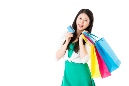 paying: young asian woman carry colorful shopping bags and online sale shopping with credit card isolated on white background over copyspace.