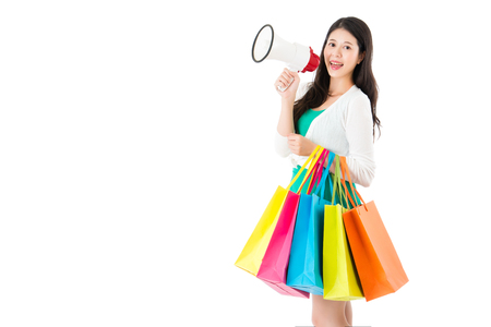 publicize: beauty shopping center female employee using megaphone publicize sale news with many color bags for client on copyspace over the white wall.