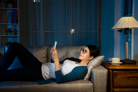 tiring female businesswoman watching mobile phone relaxing on the living room lying down on the sofa with copyspace drinking hot coffee resting moment for working over night.