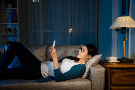 vermoeide vrouwelijke zakenvrouw kijken mobiele telefoon ontspannen op de woonkamer liggen op de bank met copyspace drinken warme koffie rusten moment voor het werken gedurende de nacht.