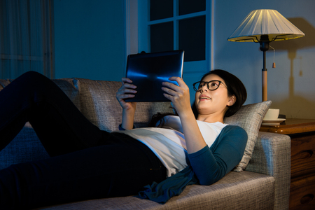 portrait of woman using digital tablet pad at night watching interesting video online and lying down on the sofa in the living room at home with holiday.