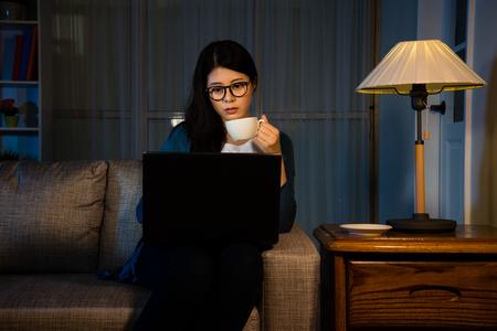 美しいビジネスの女性、夜部屋をリラックス オフィスで過労とエネルギーを高める熱いエスプレッソ コーヒーを飲むと、快適なソファの上に彼女自