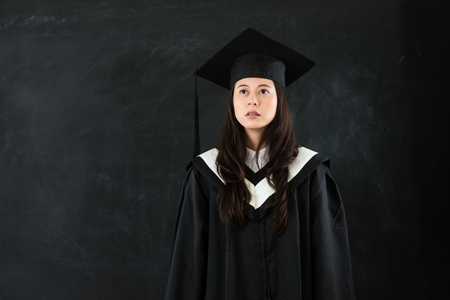 looking daze female student in black clothing and hat gaze front seem feeling unhappy for future on copyspace with chalkboard.