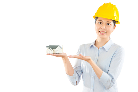 beautiful asian woman holding a model house isolated on white background presenting displaying showing in the copyspace with blank area over clean wall.
