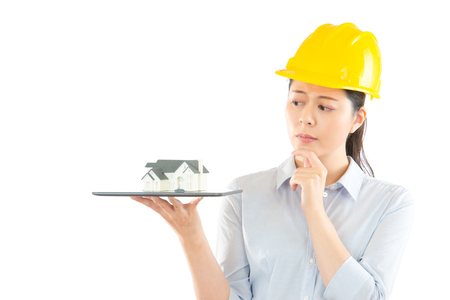 thoughtful confused builder in helmet thinking architecture design problem scratching his chin and holding pc tablet with house model isolated on a white background over blank copyspace.