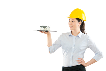 young woman model showing house model on the pad computer over copyspace in helmet playing a engineer company advertising on the white wall background. Stock Photo