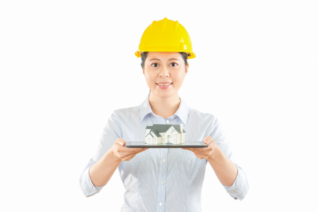 woman engineer of big blank background showing portable touch pad with miniature house model while standing in white wall with copyspace. concept of building architecture combine online technology.