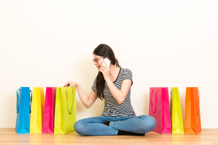 casual woman using mobile phone talking with friends checking the online shopping bags goods at home sitting on a wooden floor with white wall background over copyspace.