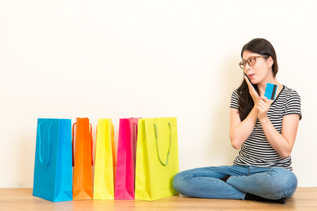 young woman shopping online through credit card electronic system when received merchandise paper bags excited sitting on wooden floor at home with white background. Stock Photo