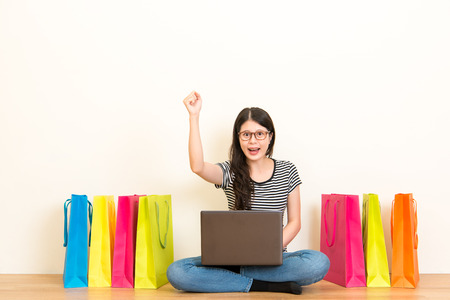 woman in the online shopping festival successfully winning the sale of goods making a happy celebration gesture on the wooden floor of the living room at home on white background copyspace. Stock Photo