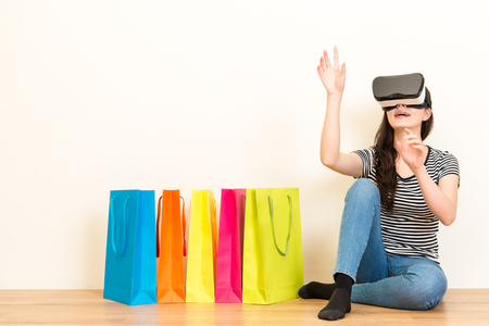 internet mall woman seller browsing personal website with 3d virtual reality device and making organize gestures to choose contents in white background with wooden floor.