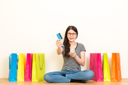 woman showing credit card sitting on a wooden floor with lots of colored shopping bags using mobile phone e-commerce transactions to buy life supplies gifts over blank copyspace on white background.