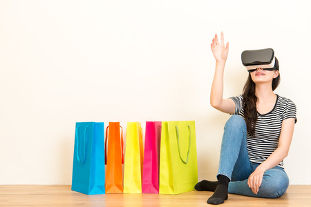 woman sitting on wooden floor with colorful shopping bags on white wall background when wearing VR device headset equipment and making grab gesture looking for goods on website.