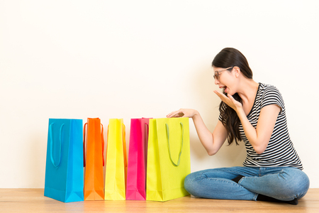 elegant girl happy receive birthday and christmas festive gifts cheerful open shopping bag sitting on wooden floor on white wall background.