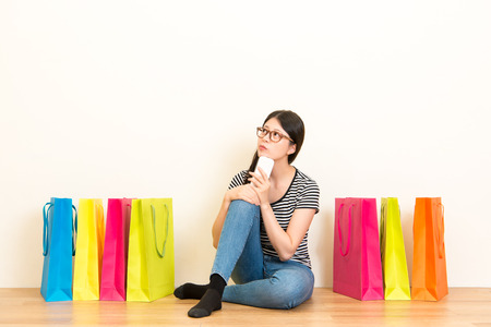 pretty girl day dream looking on the blank copyspace thinking online shopping with smartphone at home sitting on wooden floor with white wall background and many colored bags.
