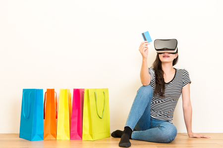 casual girl sitting on wooden floor using personal credit card e-commerce system online shopping through VR technology device on the white wall background.