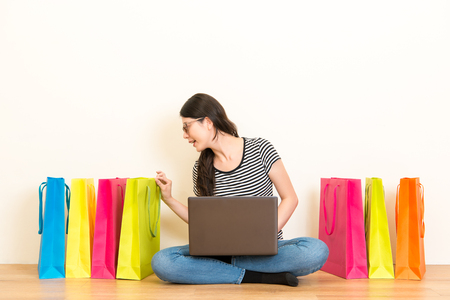 pretty female student watched checking the festive gift in the shopping bag sitting on a wooden floor using mobile computer to chat with friends on white wall background over blank copyspace area. Stock Photo