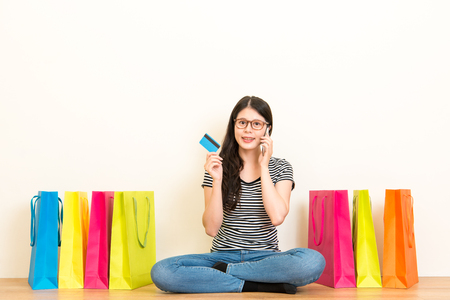 woman calling for online center to use the credit card e-commerce system shopping order gift for family sitting on the floor of the living room with wooden floor over white copyspace background wall.