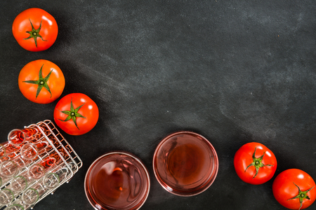 many tomato making a red liquid through science and technology experiments in the test tube showed genetic improvement on the blackboard background with blank copyspace. Reklamní fotografie