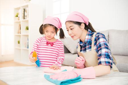 jonge Aziatische vrouw en een klein kind meisje veegde de afstoffen tafel in de woonkamer thuis. Moeder en dochter doen het schoonmaken in het huis. familie huishoudelijk werk en huishouden concept. Stockfoto