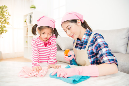 asian chinese mother and kids cleaning room together. happy family do the dusting at home. housework and household concept.