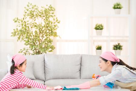 アジア中国の母と子供の演奏と一緒に、自宅のリビング ルームでクリーニングに互いに直面します。家事と家計のコンセプトです。 写真素材