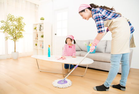 Mamá enseñando a hija a limpiar la sala de estar de su hogar durante el fin de semana. Una mujer joven y una niña pequeña desempolvando. trabajo doméstico de la familia y el concepto de hogar. Foto de archivo - 80082505