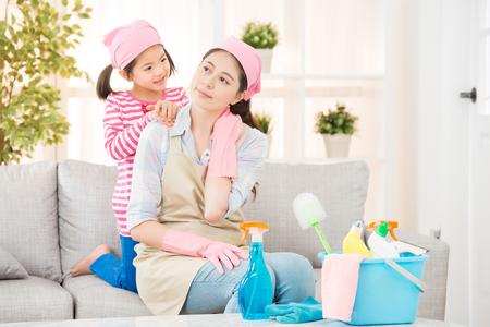 주부는 집에서 청소를 한 후 피곤하고 목이 아프다. 딸의 도움으로 마사지가 근육통을 풀어 준다. 집안일 및 가계 개념입니다.