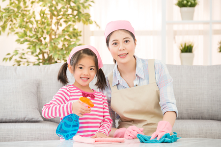 asian chinese daughter and mother happy cleaning living room together. family housework and household concept.