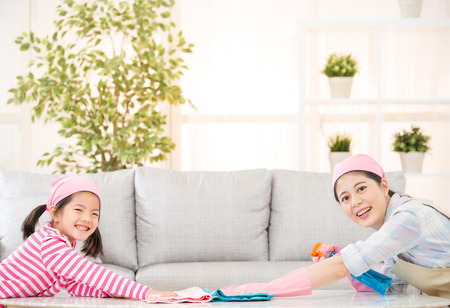 Young happy mother and her little daughter cute girl, cleaning the house together sweeping the table in a white sunny living room with modern interior. family housework and household concept.