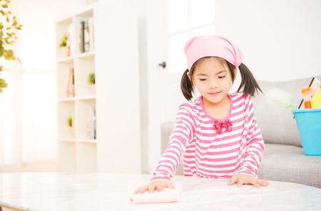 glückliches kleines asiatisches chinesisches Mädchen, das mit Lappen im Wohnzimmer zu Hause das Säubern lernt. Hausarbeit und Haushaltskonzept.