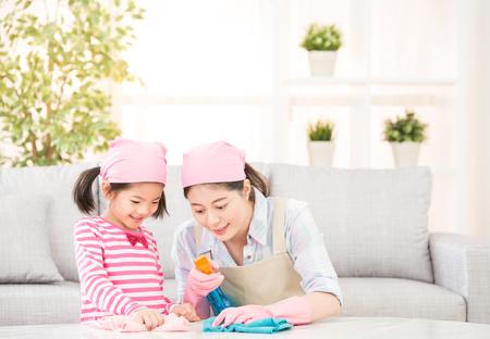 Glückliche Familie säubert das Wohnzimmer. Mutter und Tochter machen die Reinigung im Haus. Eine junge Frau und ein kleines Kind Mädchen Abstauben. Familienhausarbeit und Haushaltskonzept. Standard-Bild - 80060406